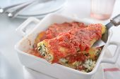 Cannelloni with spinach and ricotta under tomato sauce on a cake server