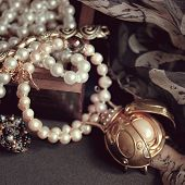 art vintage golden and pearl bijouterie with scarab on black silk background in sepia and peach; square card