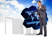 Thinking businessman with hand on chin against closed and open doors in sky