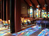 pic of church interior  - Interior of monastery church with colorful reflections of stained glass windows on floor and furniture - JPG