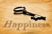 Key to Happiness on an old worn wooden desk top