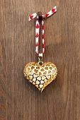 A gold heart ornament hanging by red ribbon on a rusty nail against a rustic wooden background.