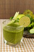 Glass of green vegetable juice and vegetables on tablecloth on bamboo background