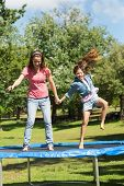 Full length of a happy girl and mother jumping high on trampoline in the park