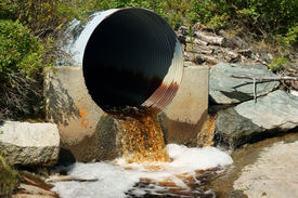 foto of water pollution  - Brown runoff rain water flowing from a rusted metal culvert into a small stream - JPG