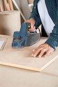 Midsection of carpenter using electric planer on wood at workshop