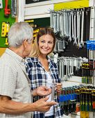 Mid adult woman with father holding wrench while standing in hardware shop