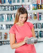 Smiling mid adult woman making payment through smartphone in hardware store