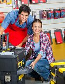Portrait of confident salesman and female customer with tool case in hardware store