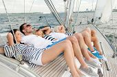 vacation, travel, sea, friendship and people concept - smiling friends lying on yacht deck