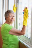 Smiling Elderly Woman Cleaning A Window