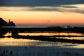 Sunset on saltpans with a church in the back (in Strunjan/Piran, Slovenia)