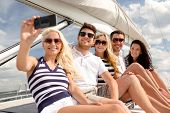 vacation, travel, sea, friendship and people concept - smiling friends sitting on yacht deck and mak