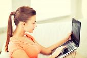 lifestyle and internet concept - woman using laptop at home