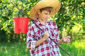 Boy wearing straw hat looking at caught fish