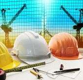 Safety Helmet On Architect ,engineer Working Table With Modern Building And Crane Construction Backg