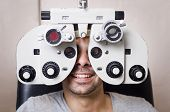 foto of exams  - Young boy in an optical scans machine exams his vision and optometry - JPG