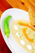 homemade cuisine : salmon vegetable soup served with bread and chives on wood