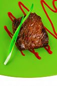 meat food : roasted fillet mignon on green plate with chives and ketchup isolated over white backgro