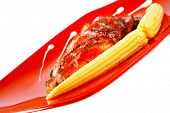 roasted beef meat with beans and corns on red plate