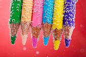 Colorful pencils in water with bubbles on red background