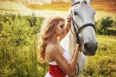 Beautiful women with white horse over sunset