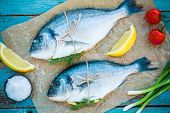 pic of fish skin  - two raw dorado fishes with lemon green onions and cherry tomatoes on a rustic background - JPG