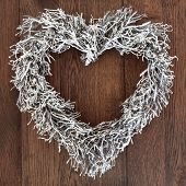 Heart shaped christmas silver wreath over old oak background.