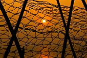 picture of fishnet  - Sun set through fishnet front ground  - JPG
