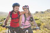Fit cyclist couple smiling together on mountain trail on a sunny day
