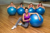 Fitness class posing with exercise balls in studio at the gym