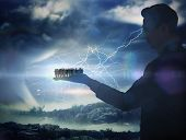 Composite image of businessman holding business team against stormy sky with tornado over landscape