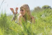 Pretty blonde in sundress lying on grass on a sunny day in the countryside