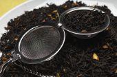 Tea strainer on heap of tea leaves