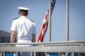 STATEN ISLAND, NY - MAY 25, 2014: A Navy officer passes the American Flag as he walks up the gangplank to the guided-missile destroyer USS Cole (DDG 067) moored at Sullivans Piers for Fleet Week NY.
