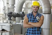 Portrait of young worker standing arms crossed in industry