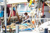 Piran, Slovenia - 15 June 2009: Woman fisher on a boat.