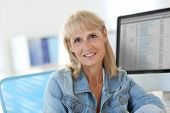 Senior woman in office working on desktop computer