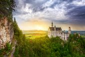 stock photo of castle  - Neuschwanstein Castle in the Bavarian Alps at sunset - JPG