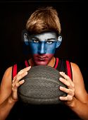 portrait of basketball player with russian flag painted on his face
