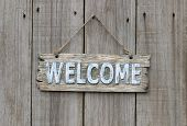 Rustic welcome sign hanging on wooden door