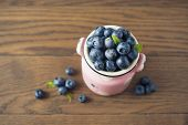 Pottery jar with blueberries on a wooden backgroun.