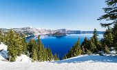 foto of wizard  - Clear blue water of Crater Lake National Park in Oregon during early spring with some snow left from winter - JPG