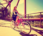 a  girl riding bikes on a bridge toned with a retro vintage instagram filter