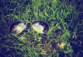 a pair of aviators on the grass toned with a retro vintage instagram filter