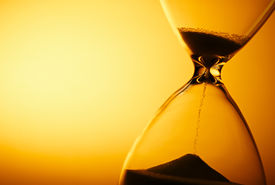 picture of pass-time  - Sand passing through the glass bulbs of an hourglass measuring the passing time as it counts down to a deadline or closure on a yellow background with copyspace - JPG