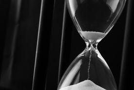 foto of pass-time  - Sand running through the bulbs of an hourglass measuring the passing time in a countdown to a deadline on a dark background with copyspace - JPG