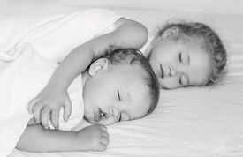 pic of matron  - charming little brother and sister asleep embracing on white background  - JPG