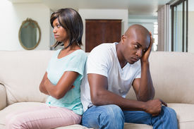 stock photo of not talking  - Unhappy couple not talking after argument on sofa at home in the living room - JPG
