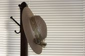 foto of racks  - This is an image of a vintage hat rack and hat against window
